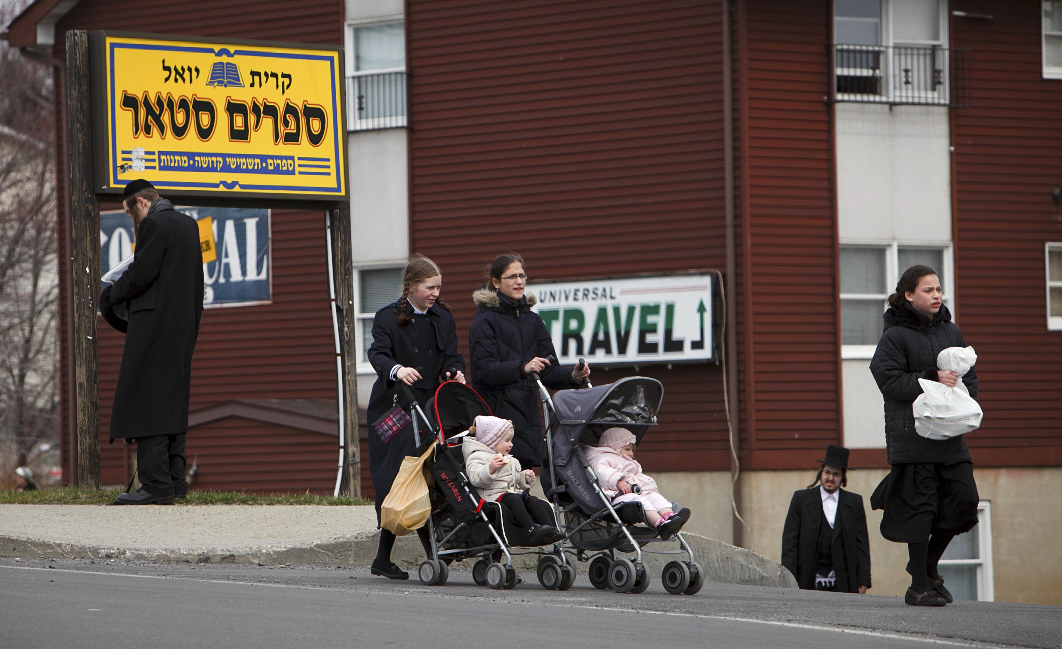 People walk along a main street in the village of Kiryas Joel, N.Y.