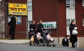 People walk along a main street in the village of Kiryas Joel, N.Y.